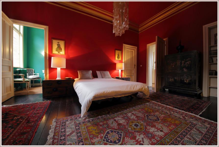 Etniczny dywan w ognistej, czerwonej sypialni.